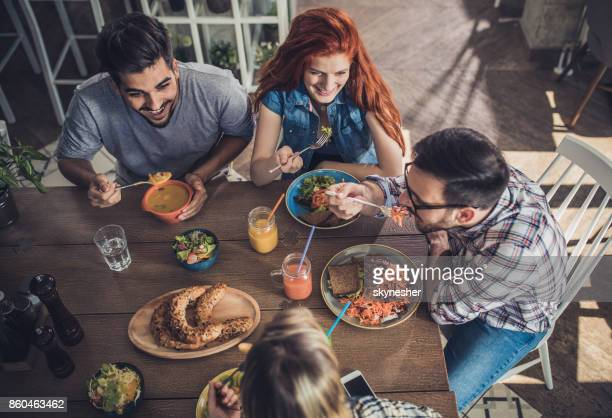 Above view of happy friends enjoying in healthy meal at a restaurant.