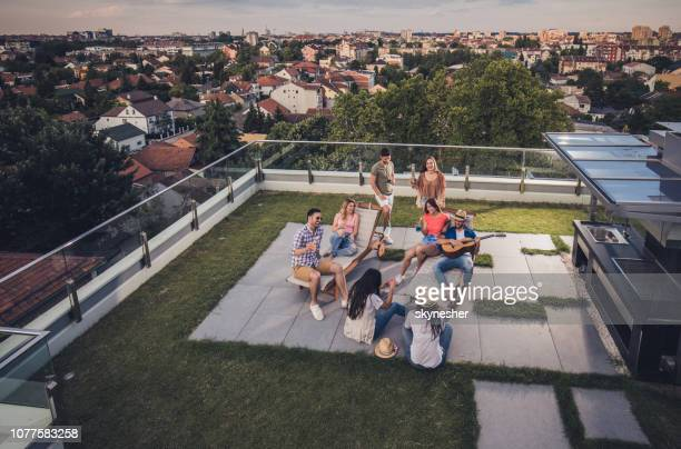 above view of happy friends having a party on a penthouse terrace. - flat stock pictures, royalty-free photos & images