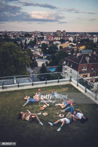Above view of happy friends relaxing on a grass at penthouse terrace.
