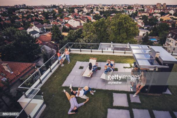 above view of happy friends relaxing on a penthouse balcony. - geographical locations stock pictures, royalty-free photos & images