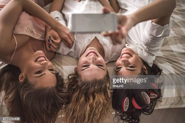 Above view of happy friends taking a selfie in bedroom.