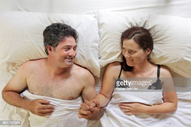 above view of happy man and woman holding hands lying in bed - rafael ben ari fotografías e imágenes de stock