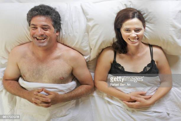 Above view of happy man and woman lying in bed