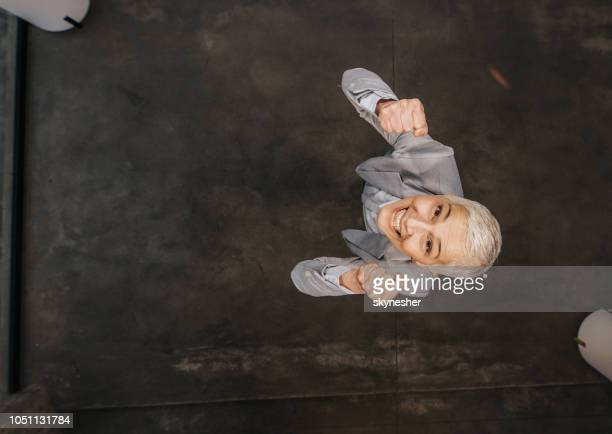 above view of happy mature woman celebrating her success in the office. - good news stock pictures, royalty-free photos & images
