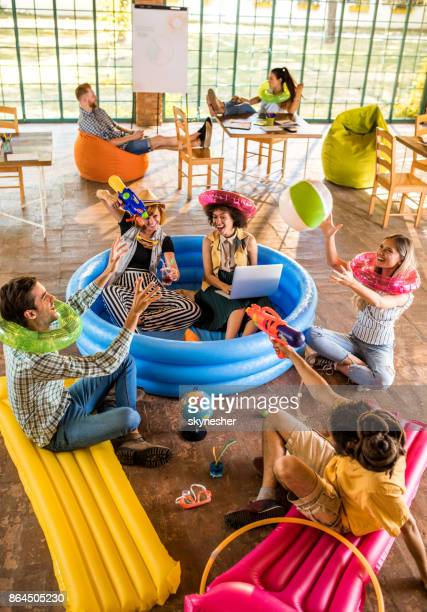 above view of happy start up team playing while waiting for their summer vacation. - adults only stock pictures, royalty-free photos & images
