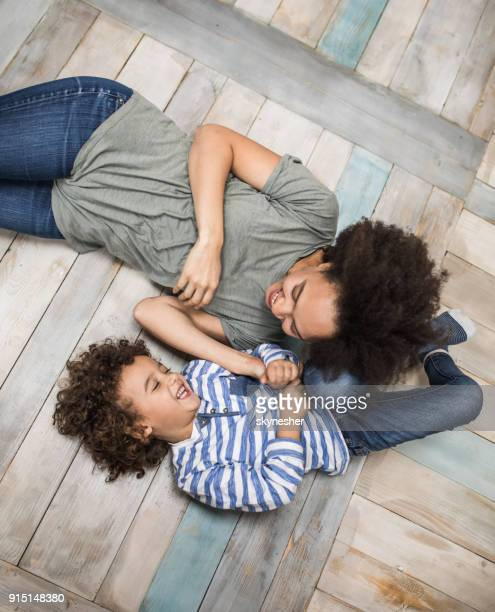 above view of joyful african american mother and son having fun on wooden floor. - tickling stock pictures, royalty-free photos & images