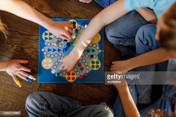 above view of kids playing ludo game. - board game stock pictures, royalty-free photos & images