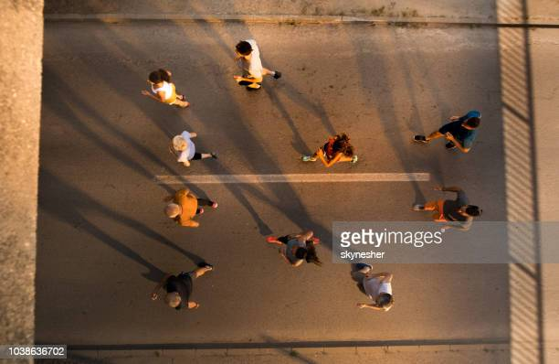 above view of large group of marathon runners having a race on the road. - half_marathon stock pictures, royalty-free photos & images