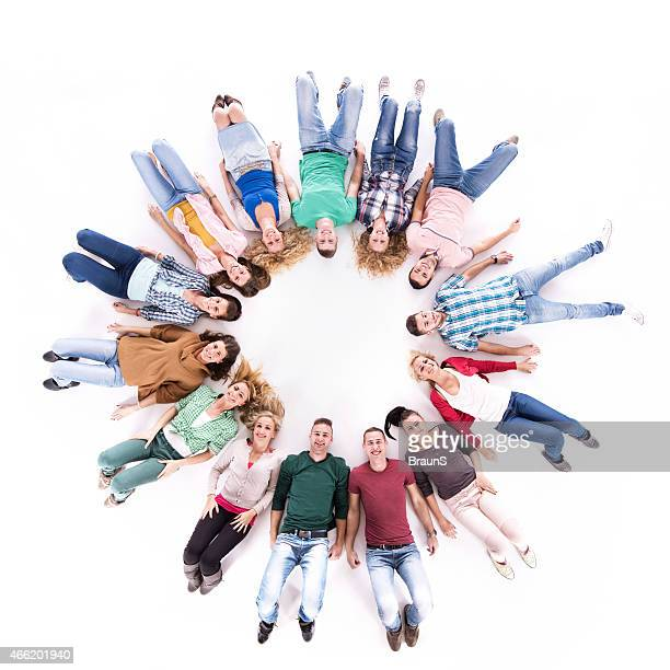 Above view of large group of people lying in circle.