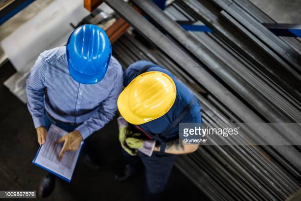 above view of manager and manual worker reading reports in steel mill. - inspector stock pictures, royalty-free photos & images