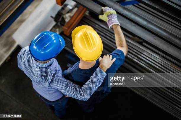 above view of manager and steel worker working in industrial building. - obscured face stock pictures, royalty-free photos & images