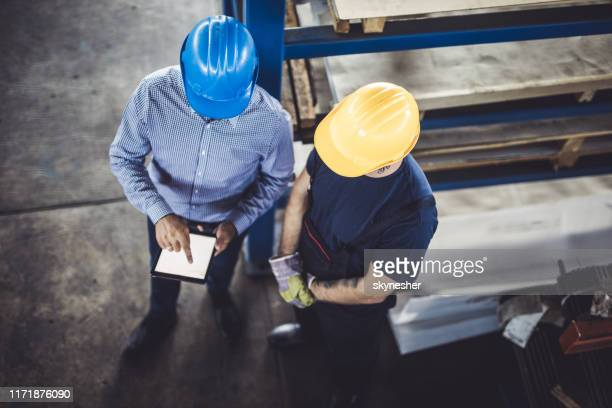 above view of manager and worker using touchpad in a factory. - obscured face stock pictures, royalty-free photos & images