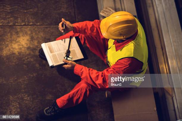 Above view of manual worker checking data in industrial building.