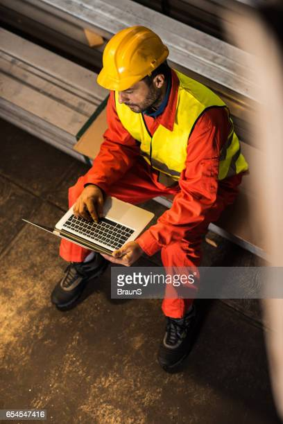 Above view of manual worker using laptop in aluminum mill.
