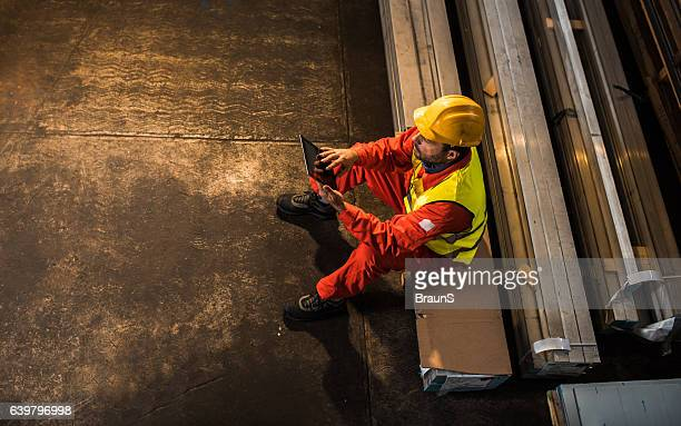 Above view of manual worker using touchpad in aluminum mill.