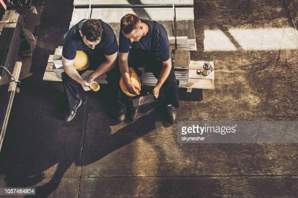 boven uitzicht van de arbeiders met behulp van de touchpad op een koffiepauze in een fabriek. - koffiepauze stockfoto's en -beelden