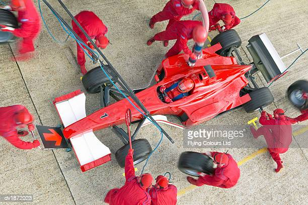 Above View of Mechanics Maintaining a Red Formula One Car at a Pit Stop