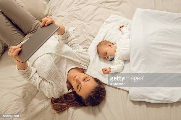 Above view of mother using touchpad next to sleeping baby.