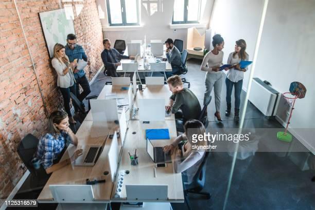 über ansicht von multi-tasking geschäftsleute in der konzernzentrale. - papierkram stock-fotos und bilder