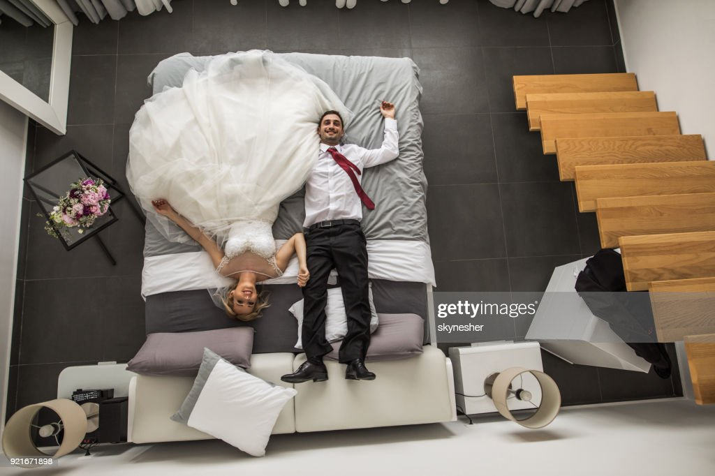 Above View Of Newlyweds Relaxing On A Bed In Their Bedroom Stock