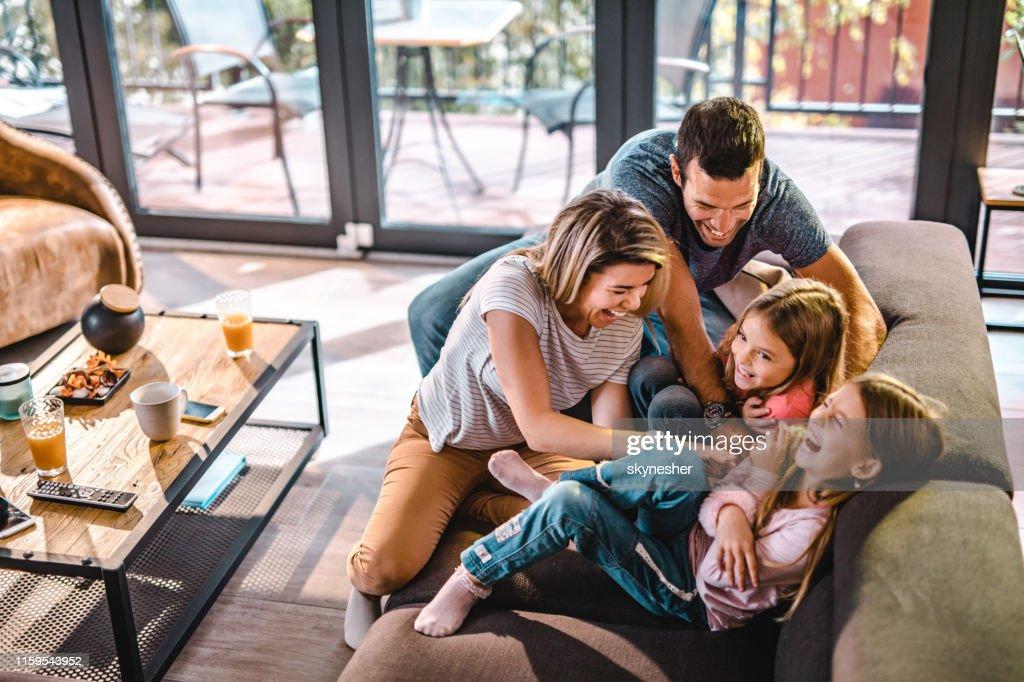 Oben der Blick auf verspielte Eltern, die ihre Töchter zu Hause kitzeln. : Stock-Foto