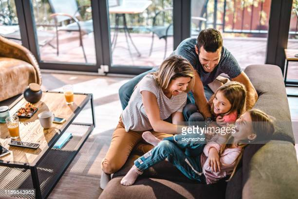 above view of playful parents tickling their daughters at home. - família imagens e fotografias de stock