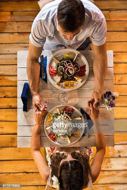 Above view of romantic couple holding hands at dining table.
