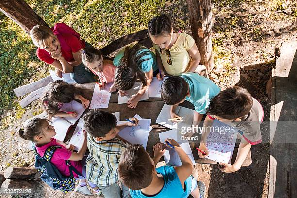 Above view of school children drawing on a field trip.