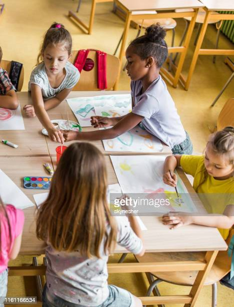 above view of schoolgirls painting with water colors on art class at elementary school. - elementary age stock pictures, royalty-free photos & images