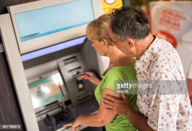 Above view of senior couple withdrawing money from cash machine.