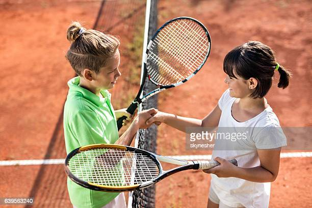 Above view of small tennis players shaking hands after match.