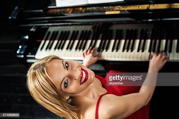 Vista superior de mulher sorridente a tocar piano.