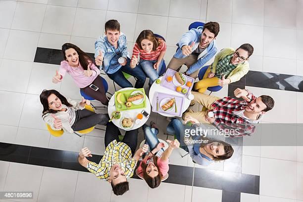 Vue plongeante d'élèves montrant thumbs up sur pause déjeuner.