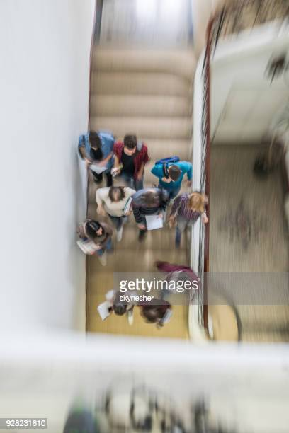 Above view of students walking down the stairs in blurred motion.