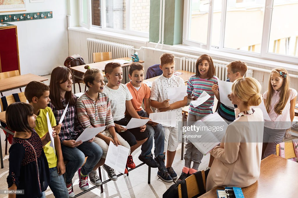 Above view of teacher singing with children during music lesson. : Stock Photo