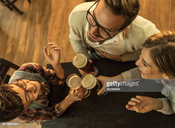 Above view of three happy friends talking in a bar while toasting.