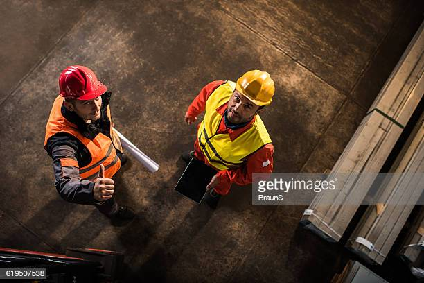 Above view of two workers standing in industrial building.