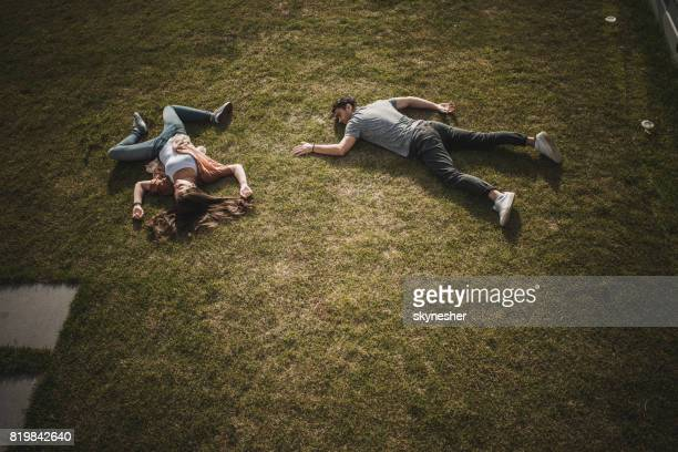 above view of unconscious couple lying on the grass. - dead man stock pictures, royalty-free photos & images