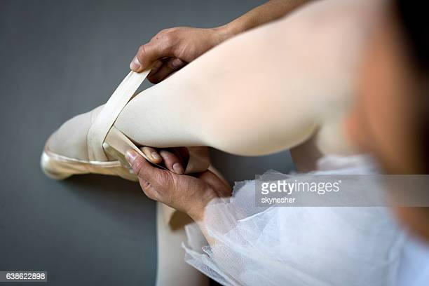 Above view of unrecognizable ballerina tying ballet pumps.