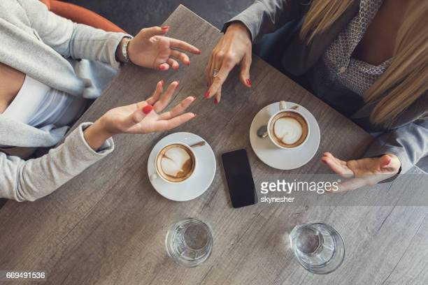 Above view of unrecognizable businesswomen discussing in a cafe.