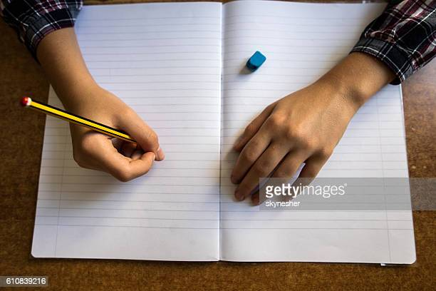 Above view of unrecognizable child writing into notepad.