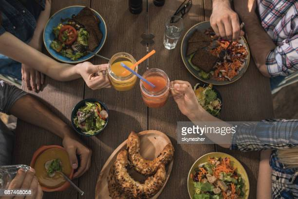 Above view of unrecognizable friends toasting with juices during lunch.