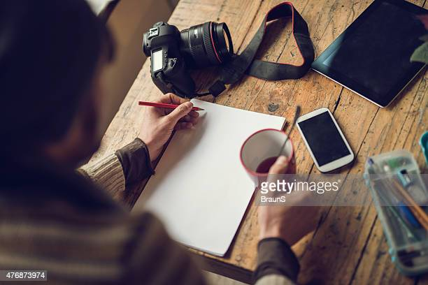 Above view of unrecognizable person writing on paper. Copy space