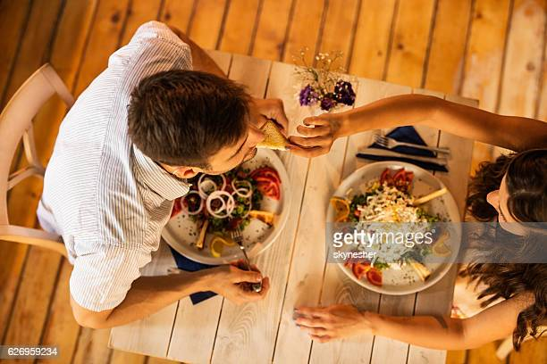 Above view of woman feeding her boyfriend during a lunch.