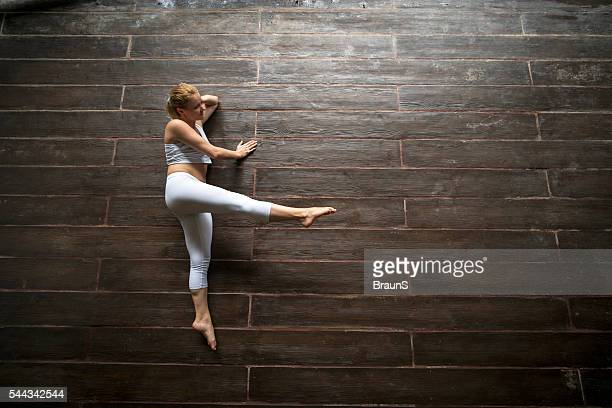 above view of young athletic woman stretching on wooden floor. - lying on side stock pictures, royalty-free photos & images