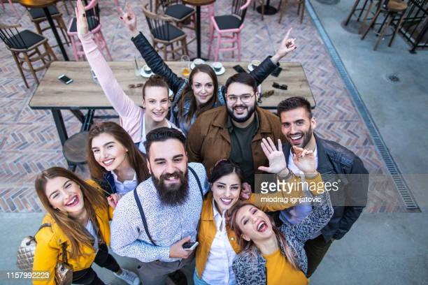 above view of young happy friends taking a selfie in a pub - waving stock pictures, royalty-free photos & images