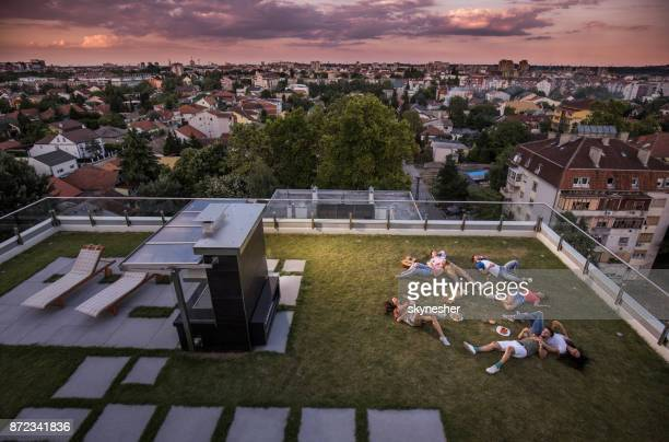 Above view of young happy people relaxing on grass at a penthouse terrace.