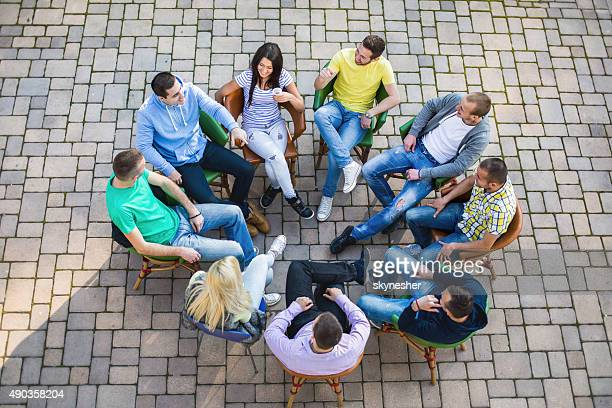 Above view of young people sitting in circle and talking.