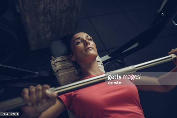 Above view of young sportswoman exercising bench press in a gym.