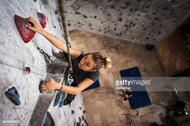 above view of young woman exercising wall climbing in a gym. - climbing stock pictures, royalty-free photos & images
